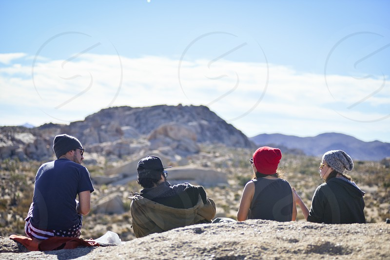 2 men and 2 women standing on rock hill under clear blue sky photo