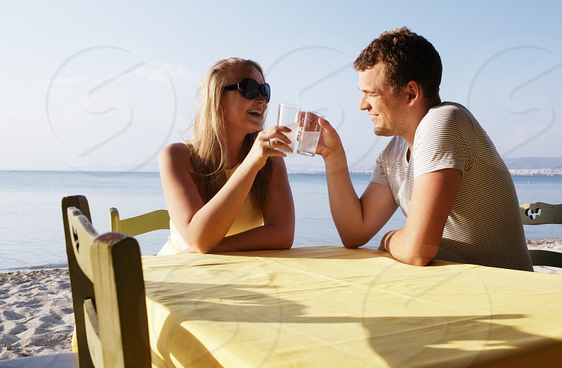 Young couple enjoying drinks at the seaside while on their summer vacation sitting at a table on the beach in the sunshine photo