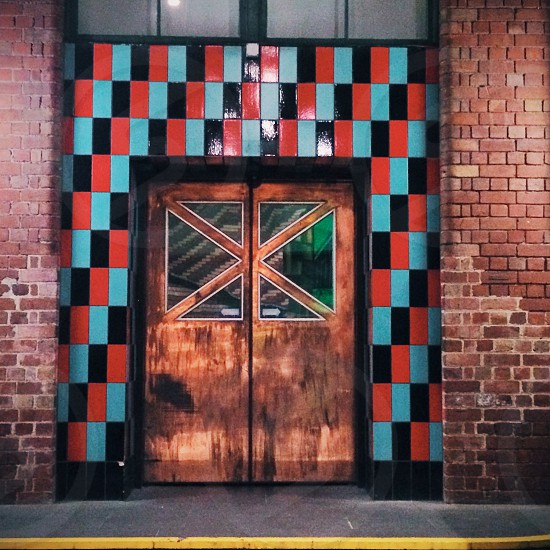 Copper door with checkerboard red black and blue tiles surrounding it RMIT building photo