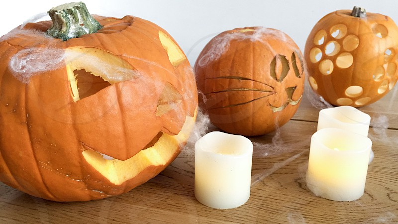 Carved Halloween Pumpkins and synthetic tealights against a white background photo