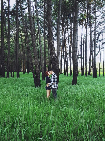 couple kissing in woods photo