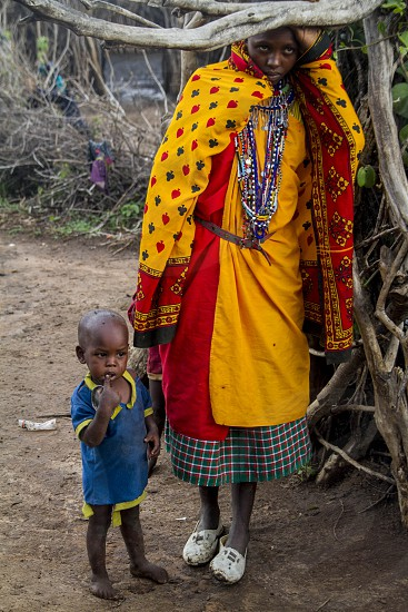 woman in red and yellow robe standing beside boy in yellow and blue polo shirt on brown dirt ground beside grey tree photo