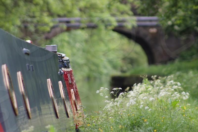 bargenarrow boatcanaloldbridgestonearchwayarchwindoswildflowersgrasswaterwaterwayrawphotographpicture photo