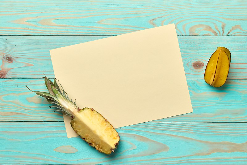 Frame decorated fresh fruit pineapple and carambola on a wooden blue background with space for text. Card. Flat lay photo