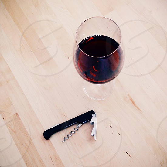 black handle cork opener beside clear drinking glass  photo