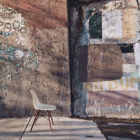 empty chair beside a wall photo