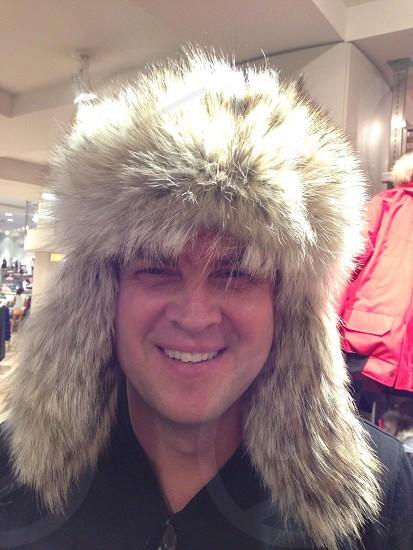 man smiling wearing gray animal fur hat photo