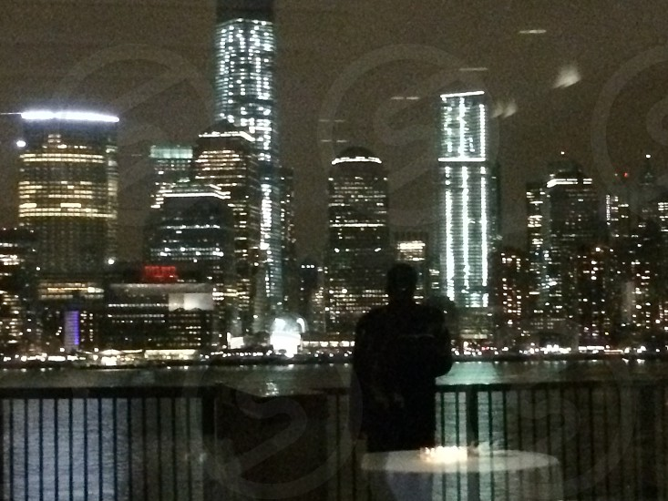 man standing on terrace and starring at city buildings at night photo