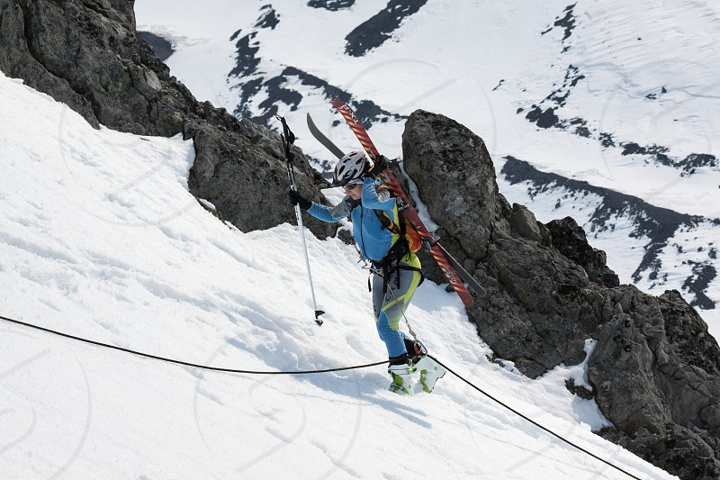 AVACHINSKY VOLCANO KAMCHATKA RUSSIA - APR 21 2012: Open Cup of Russia on Ski Mountaineering on Kamchatka - young woman ski mountaineer climbing on rope on rocky mount with skis strapped to backpack photo