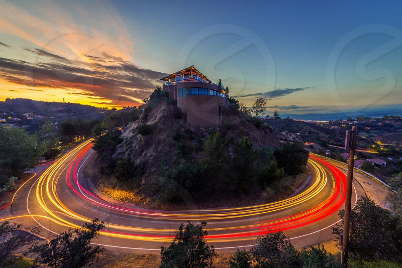 cars driving around a winding road around a home on top of a hill overlooking homes in a valley under a sunset sky photo
