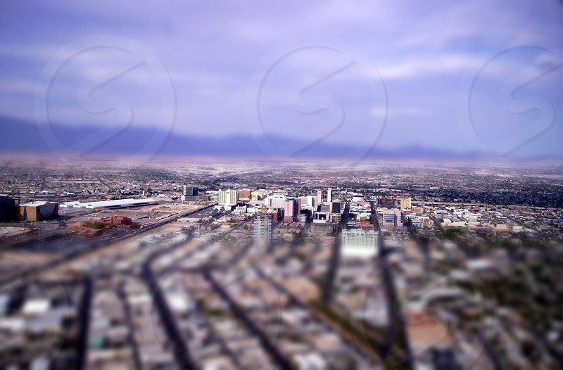 concrete buildings under cloudy sky during daytime in tilt shift lens photography photo