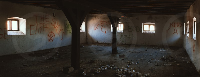 Abandoned old dirty and dark large room interior view during day.  photo