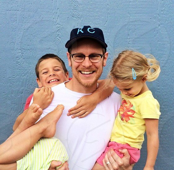 blonde man with glasses wearing white t-shirt holding 3 children photo
