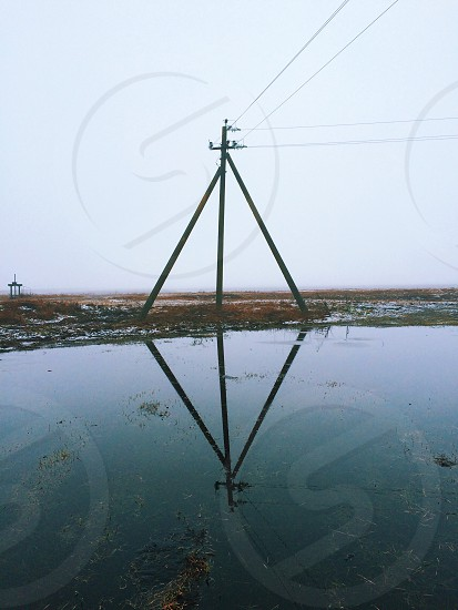 black electric outpost near body of water under cloudy sky photo