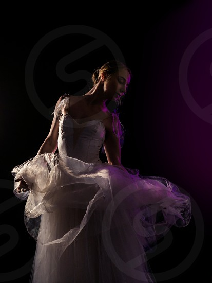 graceful ballerina in white tutu dress dancing elements of classical or modern ballet in the dark with neon light and smoke on the black background. art concept. photo