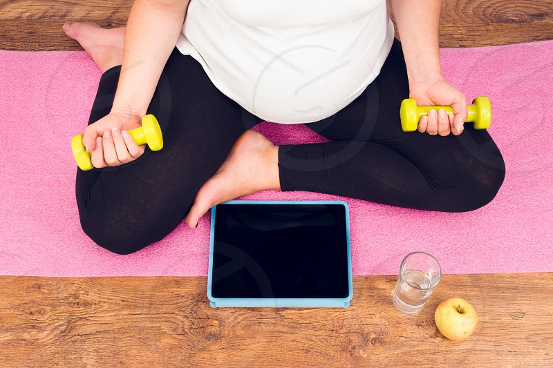 Active pregnant woman with dumbbells exercising with video course photo