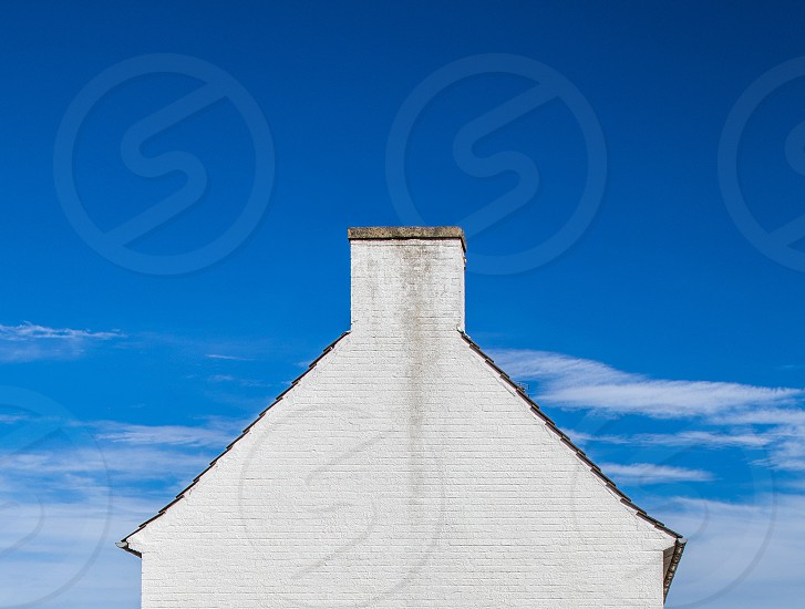 Stark contrast of a White Scottish cottage against the bright blue sky with scattered clouds. photo