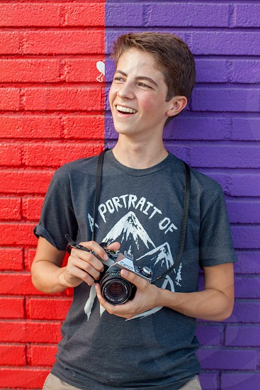 boy in grey crew neck t shirt leaning on red and purple painted brick wall holding canon camera photo