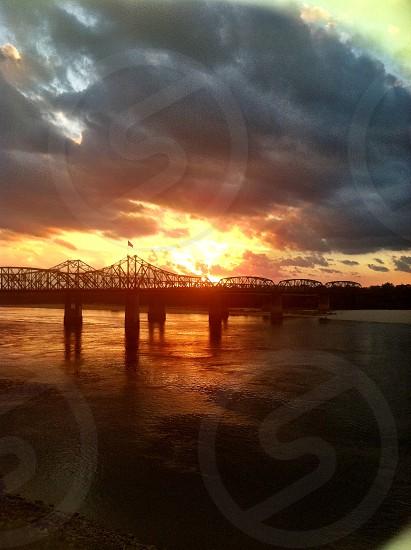 sunset over bridge over ocean photo