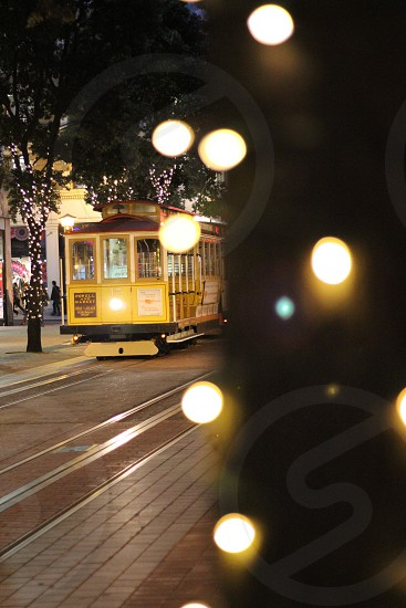 Cable car in San Francisco during Christmas season surrounded by trees with Christmas lights in their trunks. photo