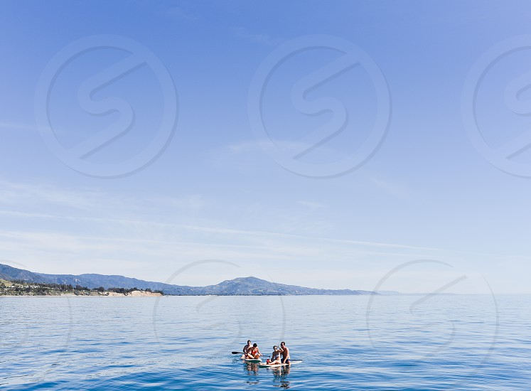 4 people in 2 canoes out at sea during daytime photo