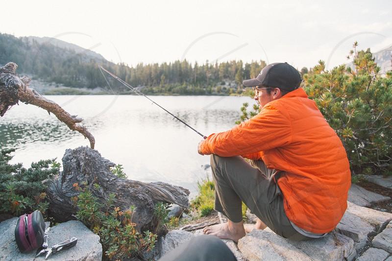 man in orange bubble jacket sitting on concrete step stool holding fishing rod while fishing during daylight photo
