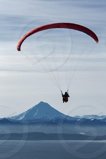 KAMCHATKA PENINSULA RUSSIA - NOVEMBER 21 2014: Paraglider flying on the background of the Viliuchinsky Volcano (Viluchinsky Volcano) and Avachinskaya Bay (Avacha Bay). photo