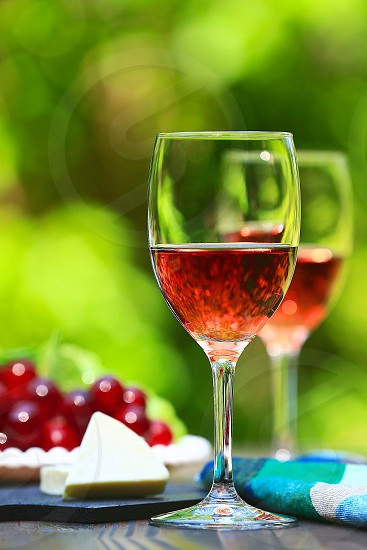 beverage bokeh bright cheese copy space drinks DSLR camera flatware fresh fruit grapes greenery background hero shot longitudinally long natural daylight no branding outdoor pink portrait rose wine Rosé Wines rustic wood surface rustic wood table Summer feeling Summer tone sun peeking through tablecloth trees background vertically long wine wine glasses photo