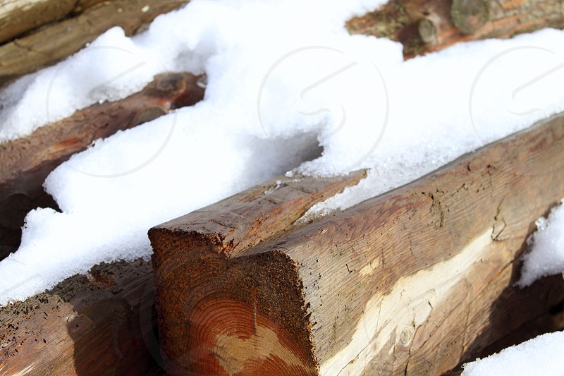 snow on wooden beams in winter wet wood photo