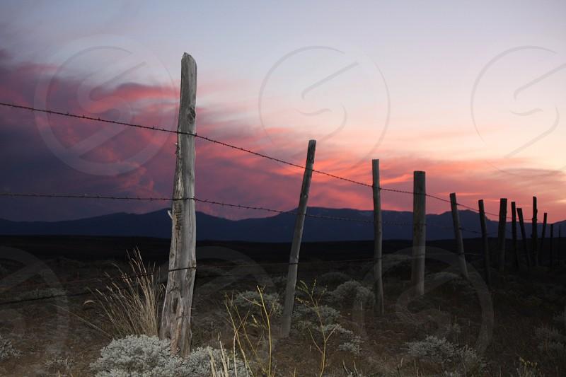 sunset ranch weather fence orange blue green post wood mountain range photo