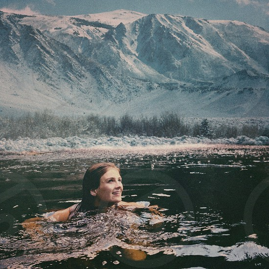 woman swimming with mountain covered with snow photography photo