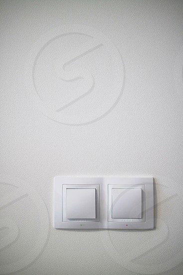 Double white lighting switchs on concrete wall electrical power socket and plug switched with copy space photo