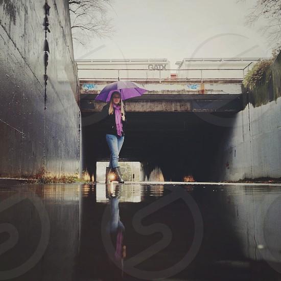woman with purple umbrella walking underneath a bridge photo