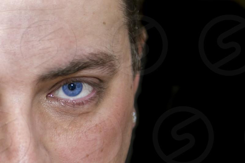 Male showing single blue eye on black background photo