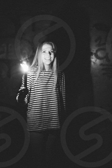 woman in white and black striped round neck long sleeved shirt holding a lighted candle photo