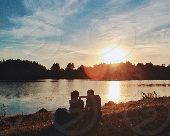 two people sitting on the edge of a lake overlooking trees across the lake with the sun shining in the distance photo