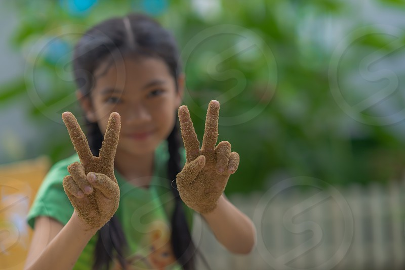 Girl with sand on her hands shows peace sign. photo