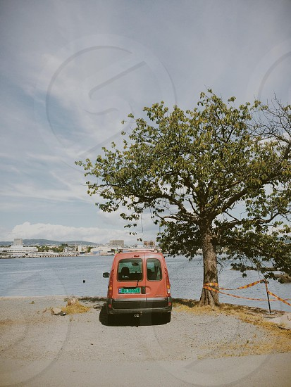 Orange Van Parked Next to Tree photo