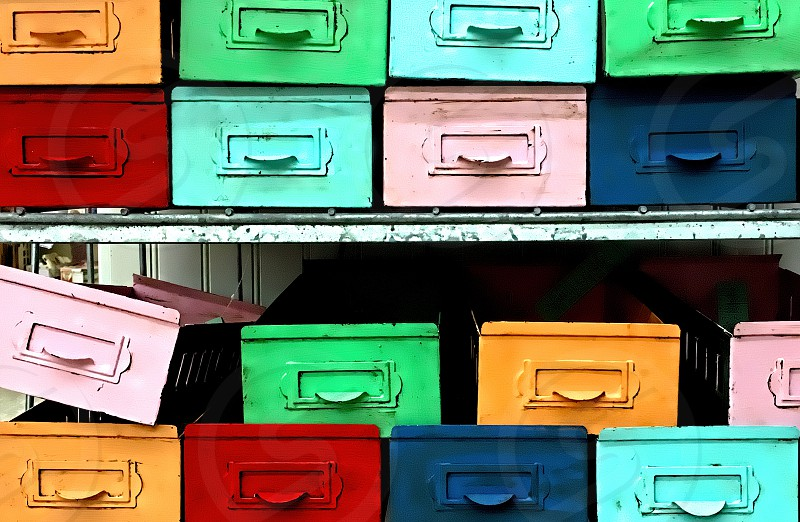 Brightly colored metal safety deposit boxes line rows of shelves. photo