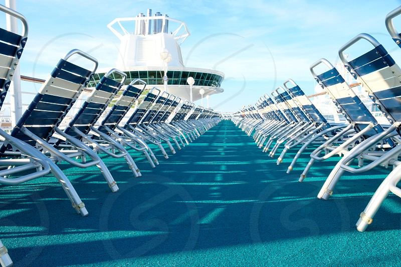 Long low angle view of a row of deck chairs on board ship. photo