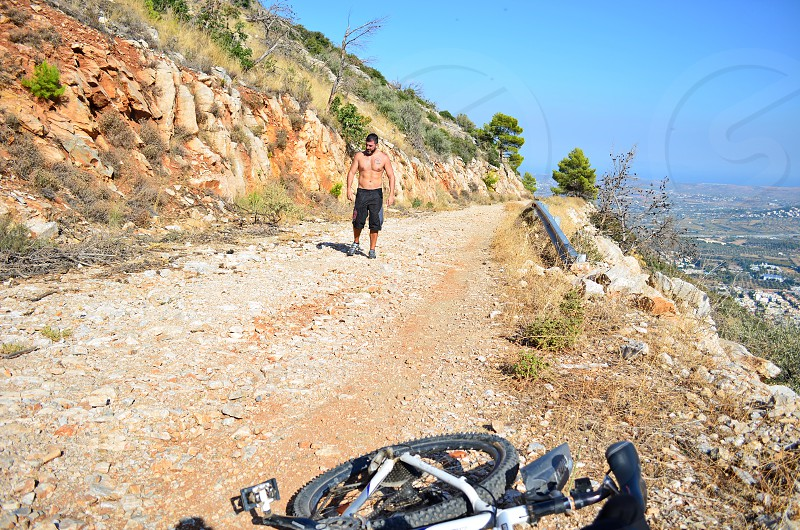 A bike and a man lost in the mountain on a very hot day photo