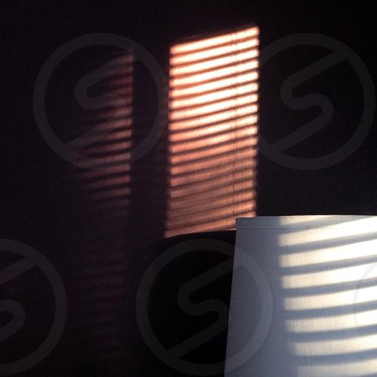 sunlight through opened venetian window blinds in dark room photo
