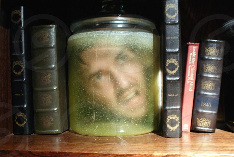 man's face print in clear glass jar between black and grey thick books photo