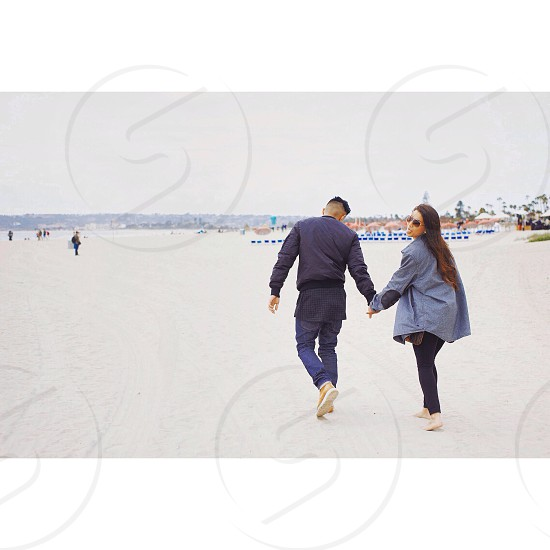 man and woman holding hands while walking photo