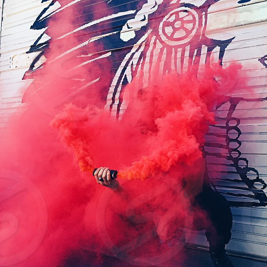 person holding black can with red smoke in front of white concrete wall with black graffiti during daytime photo