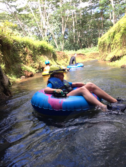 blue float ring ridden by woman as she drifts along the river together with other two people during daytime photo