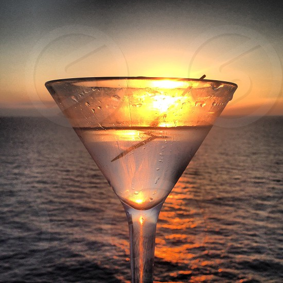 sunset behind clear martini glass photo