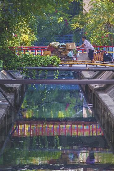 Thailand bridge crossing reflection worker cart photo
