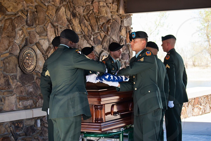 man wearing green military suit standing beside brown coffin photo