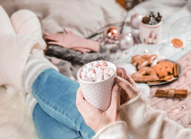 Christmas decorations blonde woman cup marshmallow gingerbreads bed cozy home indoor hands legs  photo